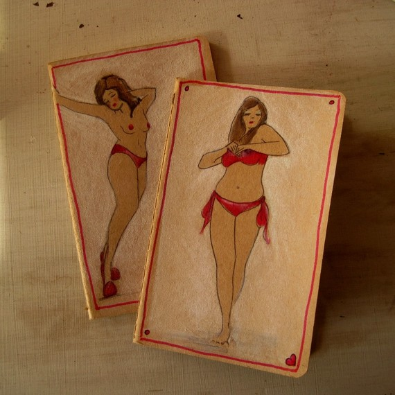 Photo of two brown covered Moleskin cahier notebooks with drawings of pin up girls on each cover.
