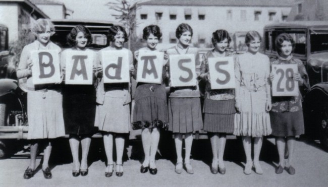 "A black and white photo presumably from 1928 of eight women holding up letters that spell ""BAdASS '28""."