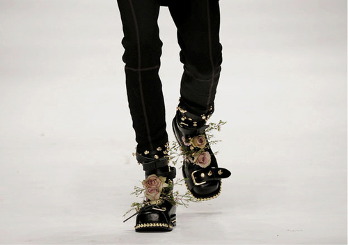 Photo of two black skinny jean clad legs walking down a white catwalk wearing big black boots with straps and pale pink roses with baby's breath tucked into the front of them.