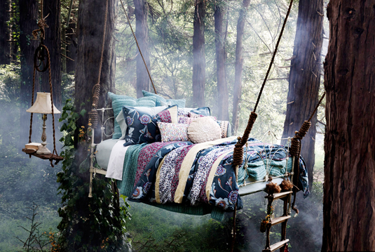 A photo of a bed with a handmade quilt and lots of cushions that is suspended by rope from trees in the middle of a forest.