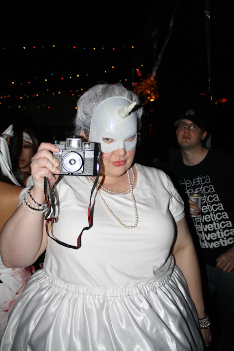 Photo of me holding up a Holga camera, while a guy in the background photobombs.