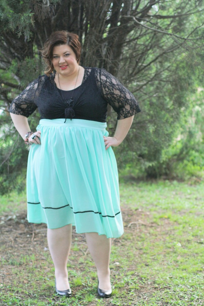 Outfit photo of me in a dress with a black top and full pale blue skirt, and a lace cardi tied under my boobs. My hair is curled and I'm wearing black shoes.