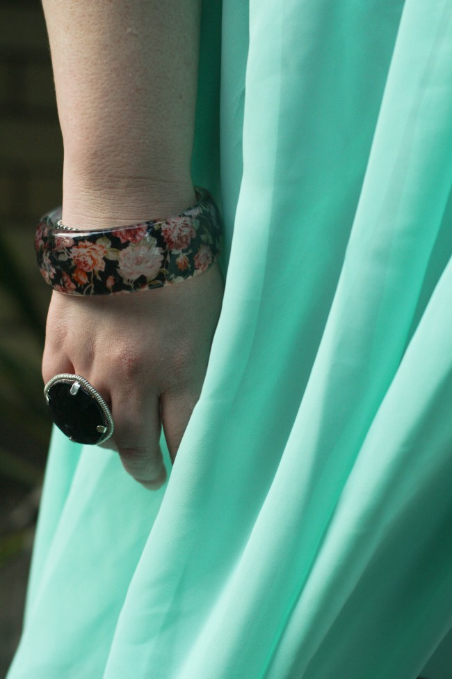 Close up photo of my hand next to my side, draped in pale blue chiffon, and I'm wearing a plastic bangle with a floral print, and a ring with a large flat dark stone.