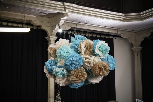 Photo of large blue, fawn and cream coloured pom poms hanging in a huge bunch from the ceiling of a large room