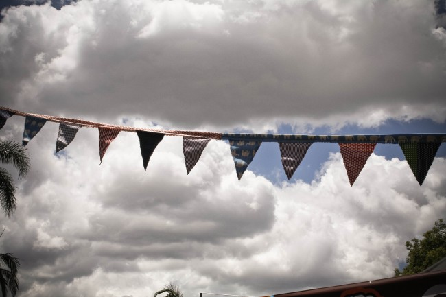 Photo of colourful fabric bunting strung up outside against large white clouds in a blue sky.
