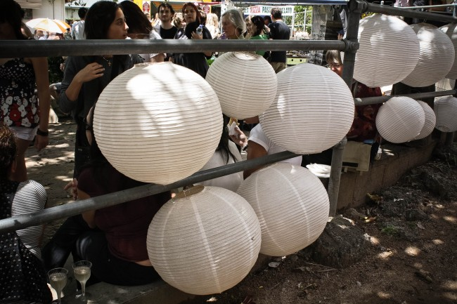 Photo of white lanterns of various sizes hung up on railings, with lots of people milling about in the background.