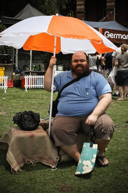 Photo of Nick, a pale skinned fat man with an amazing beard, sitting on a hession covered milk crate holding up a large orange and white umbrella.