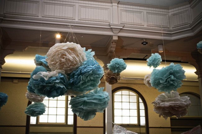 Photo of large blue, cream and fawn pom poms hanging from the ceiling of a very large room.