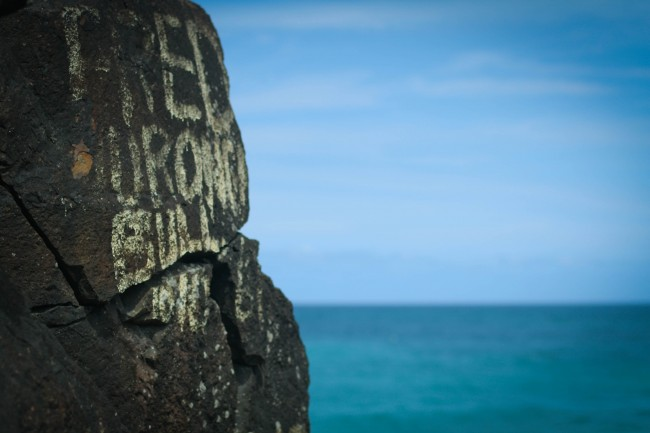 """Photo of a huge rock with graffiti that is quite old and weather worn, the only legible word says """"FRED"""". In the background is a blue green sea meeting the blue sky with feint clouds stretching across it."""