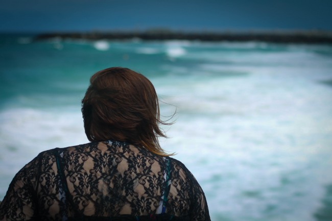Photo of the back of me sitting on rocks facing the sea, I'm wearing a black lacey top and my hair is a little bit windswept.