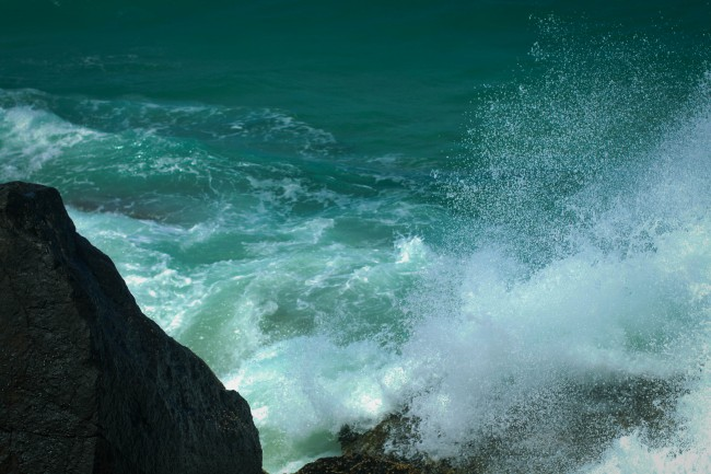 Photo of white foamy waves crashing against rocks, with the sea beyond a rich teal colour.