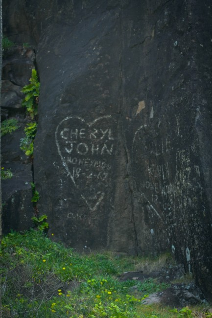 """Photo of white painted graffiti on a rock face that says """"CHERYL JOHN HONEYMOON 8-2-67"""" with a heart around the words."""