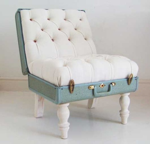 Photo of a seat made from a lovely plush white quilted padding on the inside of an old opened mint green suitcase with ornate white legs attached to the bottom.