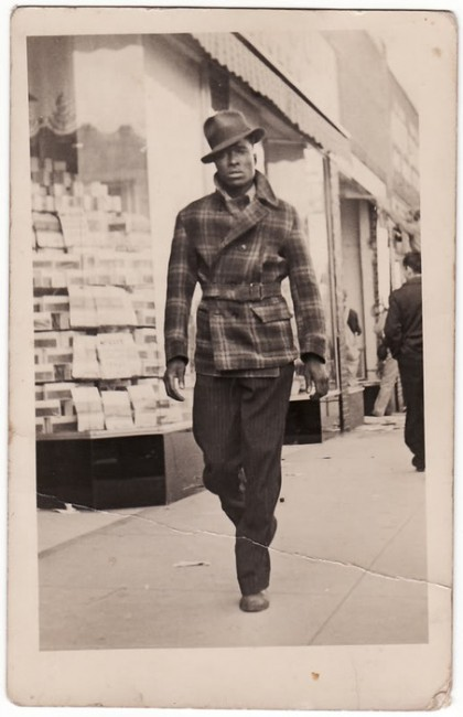 A sepia toned vintage photograph of a young slim dark skinned man wearing a checked jacket belted at the waist with a turned up collar, pin stripe pants and a jaunty hat. He is  strutting down the footpath with confidence but looking at the photographer questioningly.