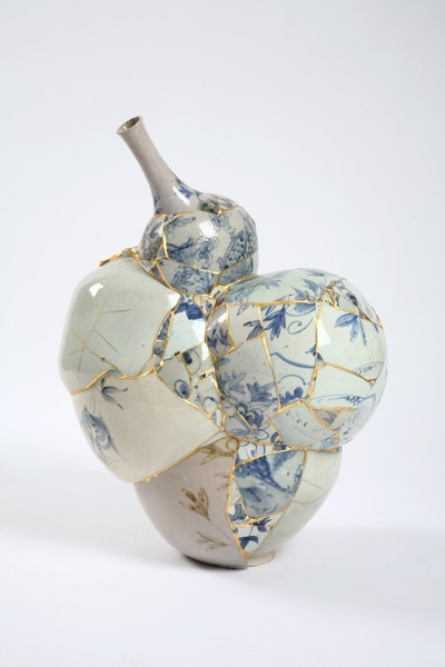 Photo of a small vessel that has been constructed out of bits of smashed china. It's got a sort of blobular form with a small funnel emerging from the top at an angle. All the seams are painted gold and highlight the disjointed construction.