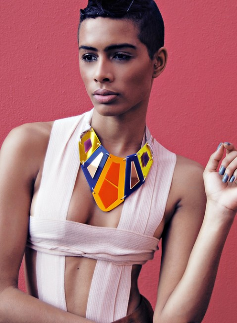 Photo of a young thin person with coffee coloured smooth skin wearing a bandage style top and a statement necklace made from coloured acrylic in geometric shapes that sit together like plates.