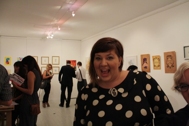 "Photo of me making a ""HIII"" face inside a small gallery with white walls."