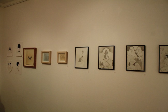 Photo of a bunch of small framed artworks lined across a white wall.