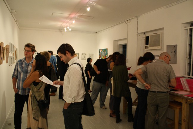 Photo of a crowd of people milling about inside a small gallery with white walls.
