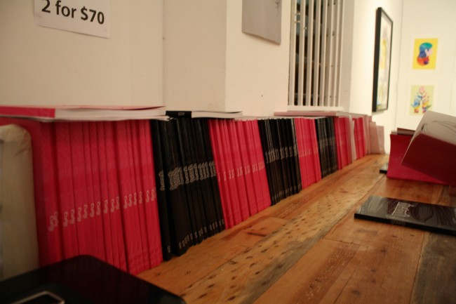 Photo of books lined up along a wall, some have pink covers and some have black covers and they alternate in chunks along the wall.