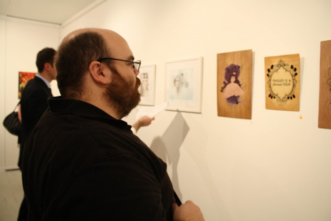 Photo of Nick staring at some artworks in a thoughtful manner. My work sits just to the left of his gaze.