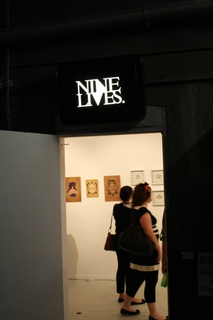 "Photo of a sign saying ""NINE LIVES"" over a doorway which you can see through to an art gallery where some of my works are hanging."