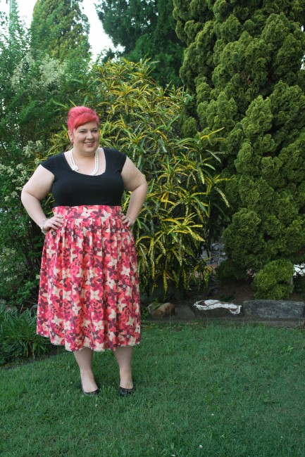 An outfit photo of me in the garden. My hair is pink and in a bouffant up-do; I wear a black top tucked into a high waisted and full skirted pink patterned skirt with a white necklace and black wedge court shoes.