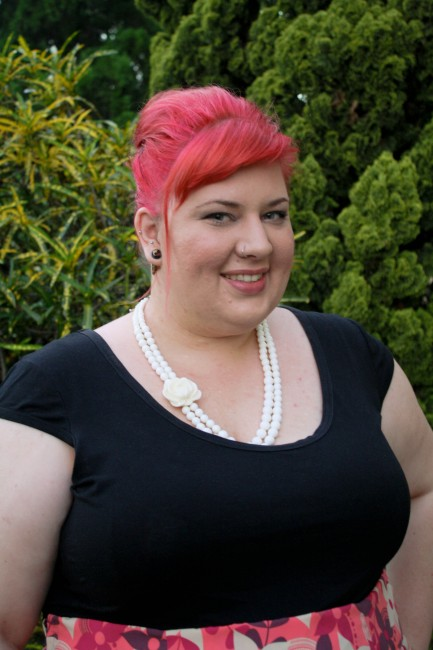 A head and shoulders photo of me  smiling with pink hair in a bouffant and a white bead necklace against a black short sleeved top.
