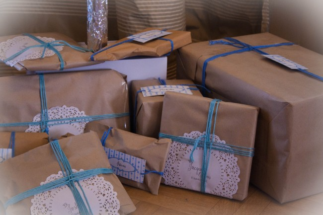 Photo of lots of brown paper wrapped presents with blue and green wool wrapped around them like ribbon.