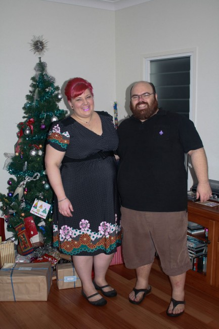 A photo of Nick and I standing to the right of a Christmas tree.