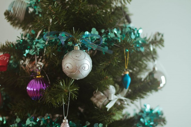 Close up photo of Mum's green (fake) Christmas tree with aqua tinsel and silver, magenta and aqua baubles hanging off the branches.