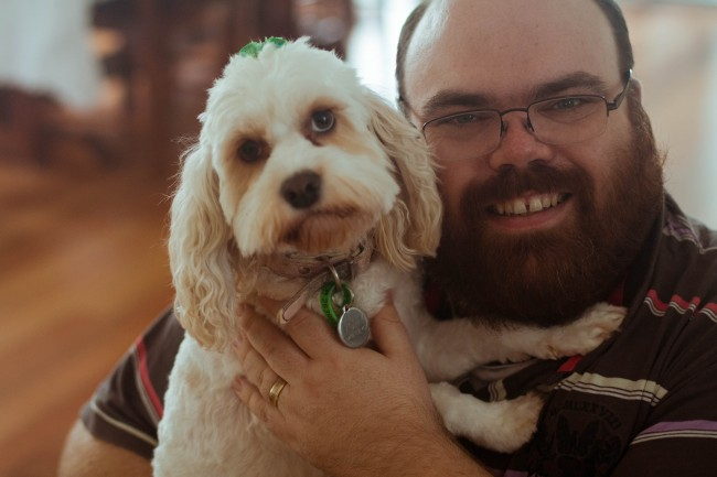 Photo of Nick, a bearded pale skinned man with glasses, holding Molly the dog whi is white and fluffy and looking at the camera dolefully.