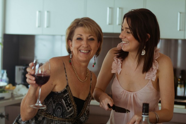 Photo of my mother, a middle aged lighted skinned woman with short light hair, and sister Amanda, a young slim dark haired woman, in the kitchen. Mum is drinking wine and smiling and amanda is holding a knife and looking at Mum and grinning.