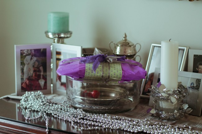 Photo of lots of photo frames, silver trinkets and a purple wrapped present sitting on a sideboard.