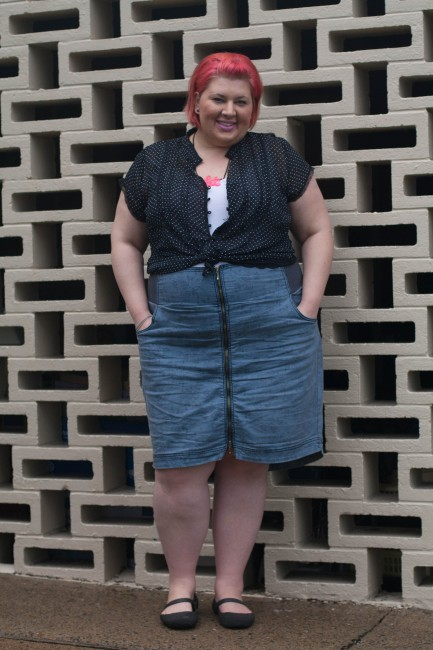 Outfit photo of me (with pink short hair!) wearing a black and white polka dot shirt over a white singlet tucked into a high waisted blue skirt with a zip up the centre. My hands are in the pockets of my skirt.