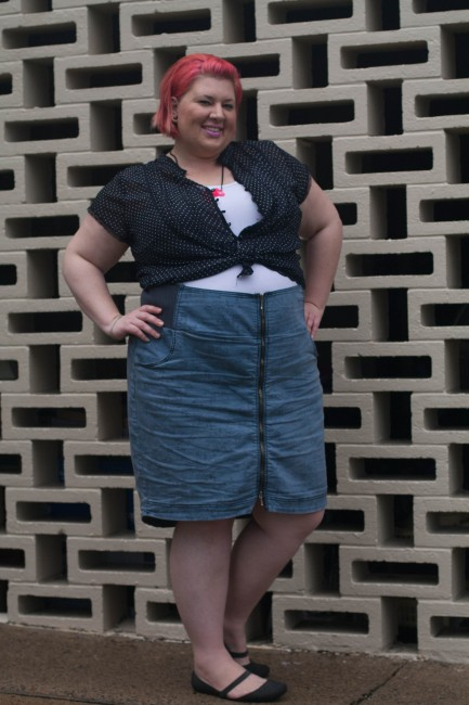 Outfit photo of me (with pink short hair!) wearing a black and white polka dot shirt over a white singlet tucked into a high waisted blue skirt with a zip up the centre. My hands are on my hips and I'm grinning.