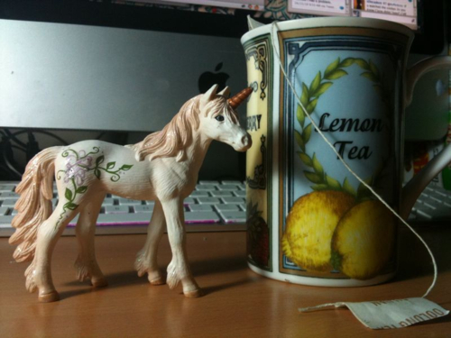 Photo of a small toy unicorn with a tea cup (that says Lemon Tea on the side).
