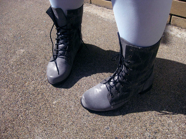 My feet and calves (in pale blue tights) wearing flat grey lace-up stompy boots.