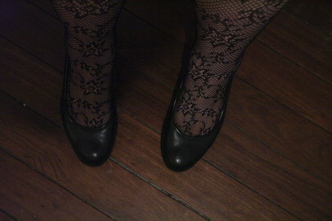 Photo of my ankles clad in lace fishnet tights and feet in black court shoes.