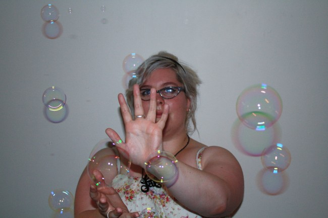 Photo of Zoe holding her hand up, seemingly pushing back a bunch of bubbles floating past her.