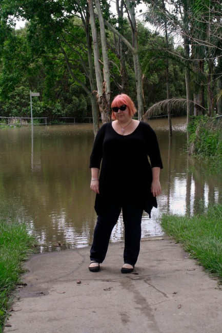Photo of me standing in front of a flooded street. I'm wearing a black tunic with jeans and my hair is a faded pink; behind me are trees extending out of the water.