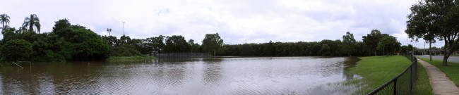 A panoramic photo of a park that has been filled with brown water. To the left are cricket cages, in the background are trees on the right side is a road and rail bridge.