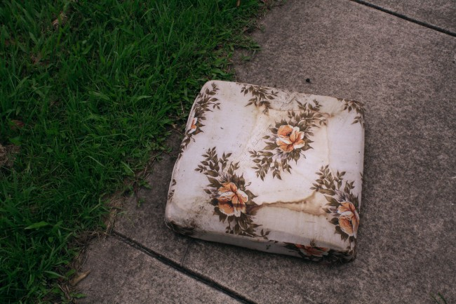 Photo of a floral covered seat cushion sitting on the footpath.