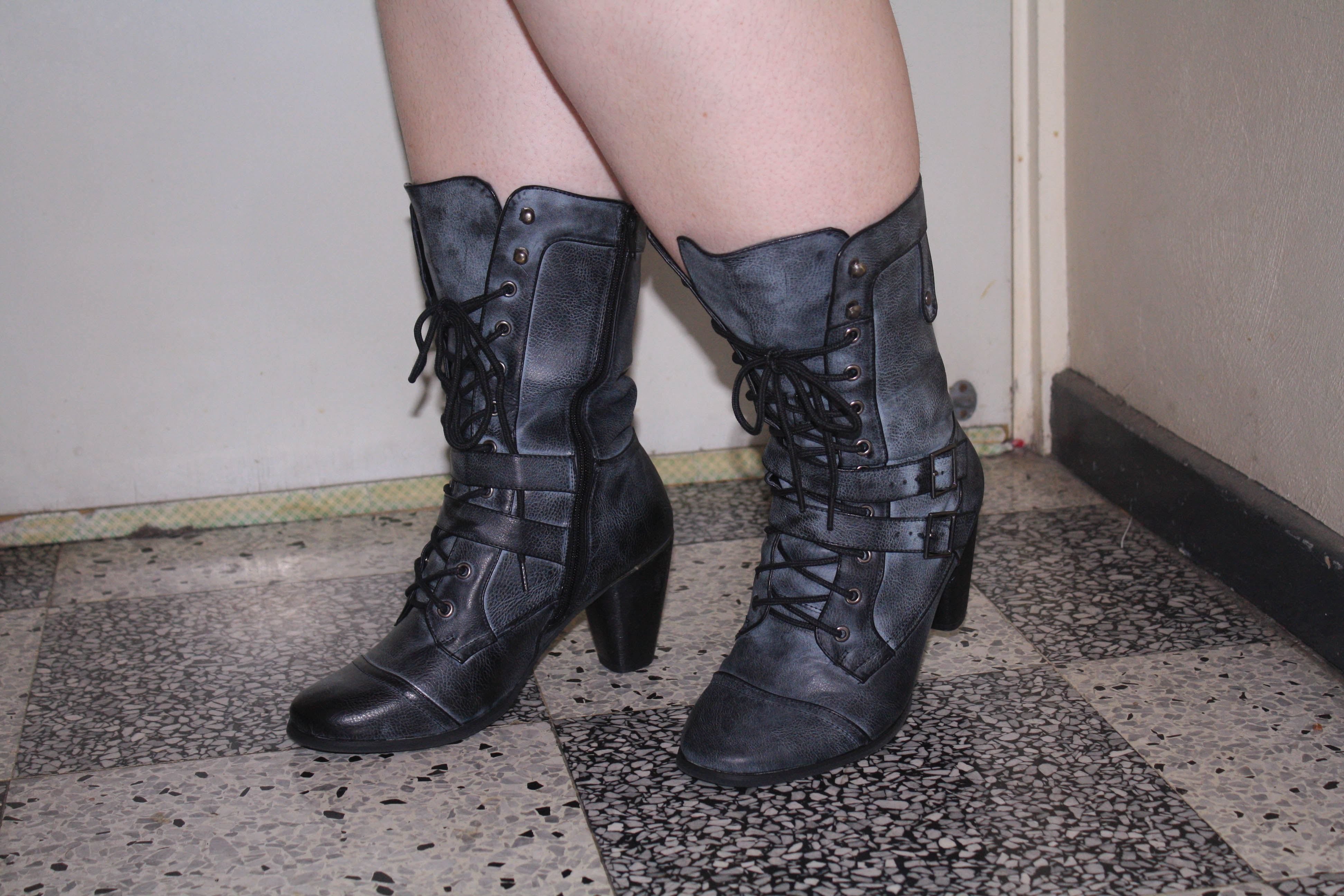 Photo of my feet and calves shod in black and grey distressed looking witchy boots. They lace up and have two tabs that reach across the foot and buckle on the other side.