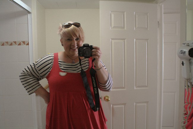 A photo of me looking into a bathroom mirror holding a DSLR. I'm wearing a black and white striped long tshirt under a pink pinafore with a white half doily brooch. My hair is now white-ish blond with an undercut and a long top and my sunglasses sit in my hair.