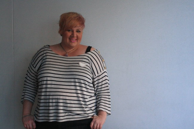 Photo of me (from the hips upward) standing against a white wall wearing a black and white striped tee with a half doily porcelain brooch.