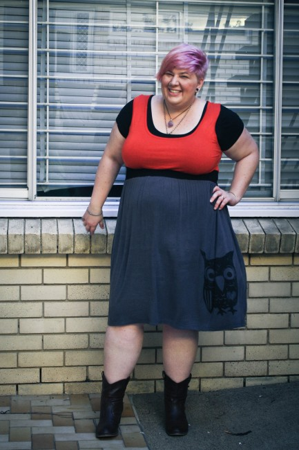 Outfit photo of me standing in front of a window with my hand on my hip. I'm wearing a black tshirt under a dress with a red top, black under bust band and grey skirt with an OWL on the bottom! Also brown cowboy boots.