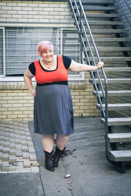 Outfit photo of me wearing the red and grey owl dress with black tshirt underneath and cowboy boots. I've got one hand on an external stairway rail and the other hand on my hip.