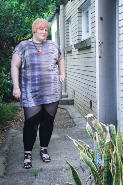 Outfit photo of me, a fat pale skinned lady, posing with one hand on my hip. I'm wearing a purple and grey tie dyed tshirt with black leggings with sheer cut outs as well as a pink fat necklace.