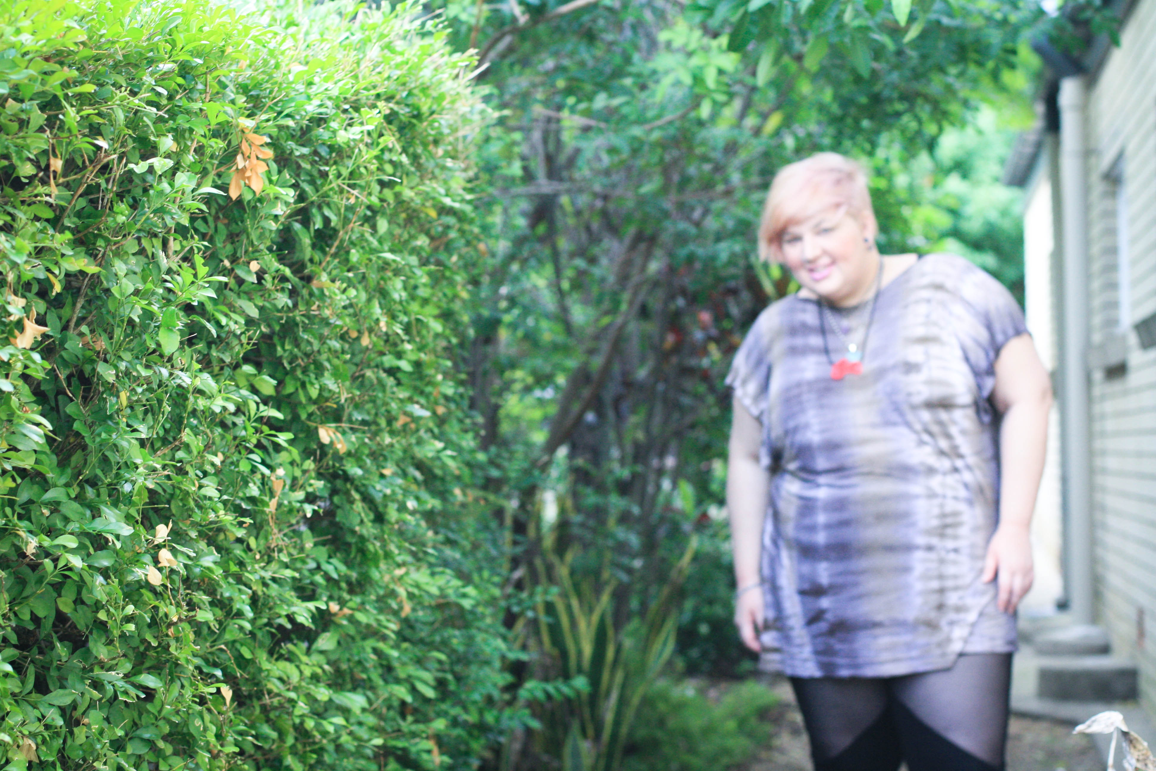 Photo of me, out of focus, standing next to a green hedge, which is in focus,